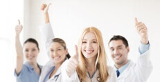 attractive female doctor with group of doctors showing thumbs up